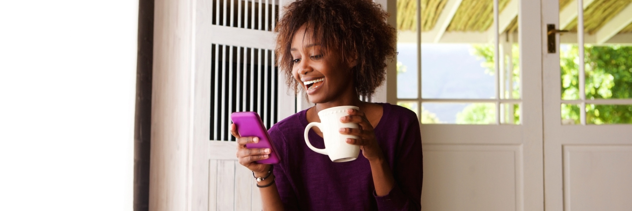 woman sitting on the floor holding a mug and smiling at her phone