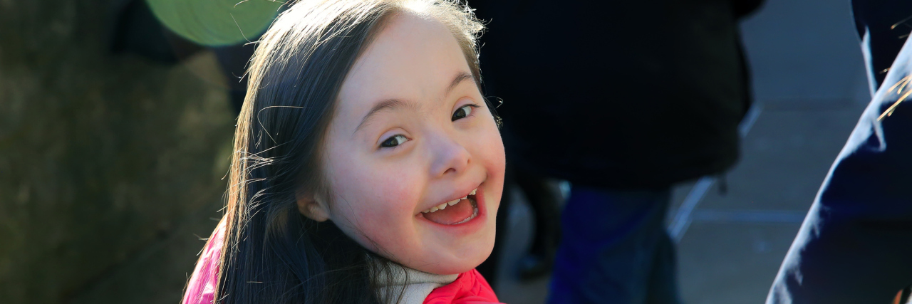 Little girl with Down syndrome smiling at camera walking away