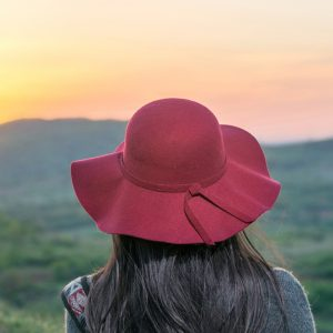 Woman wearing hat, facing sunset over mountain landscape