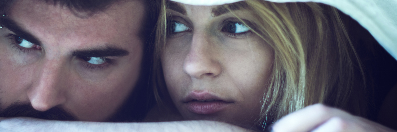 Couple laying in bed looking sad
