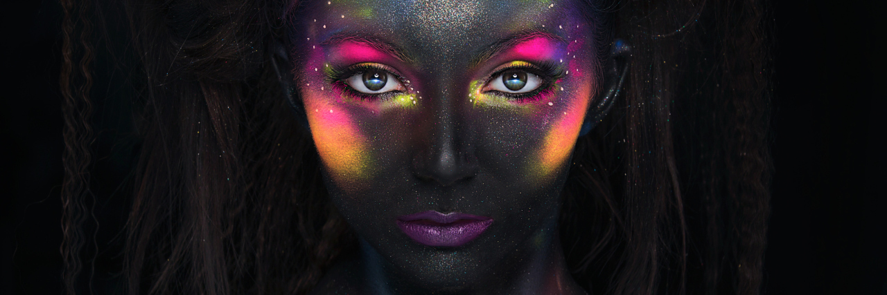 Glowing neon makeup with dramatic look.