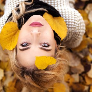A young woman looking up to the sky with autumn leaves falling towards her.