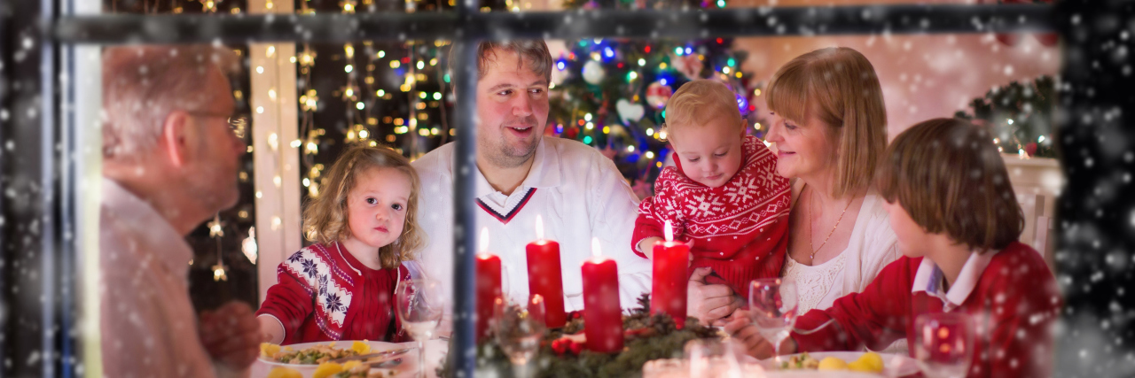 A photo looking into a window of a family at Christmas time.