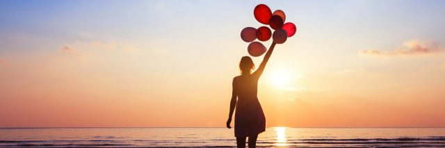 woman standing on the beach at sunset holding balloons