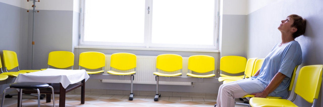patient sitting alone in waiting room yellow chairs