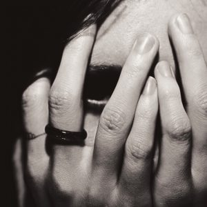 Portrait of a woman covers her face with hands