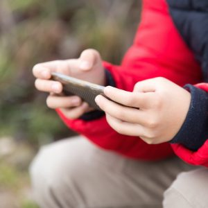 boy holding cell phone outdoors