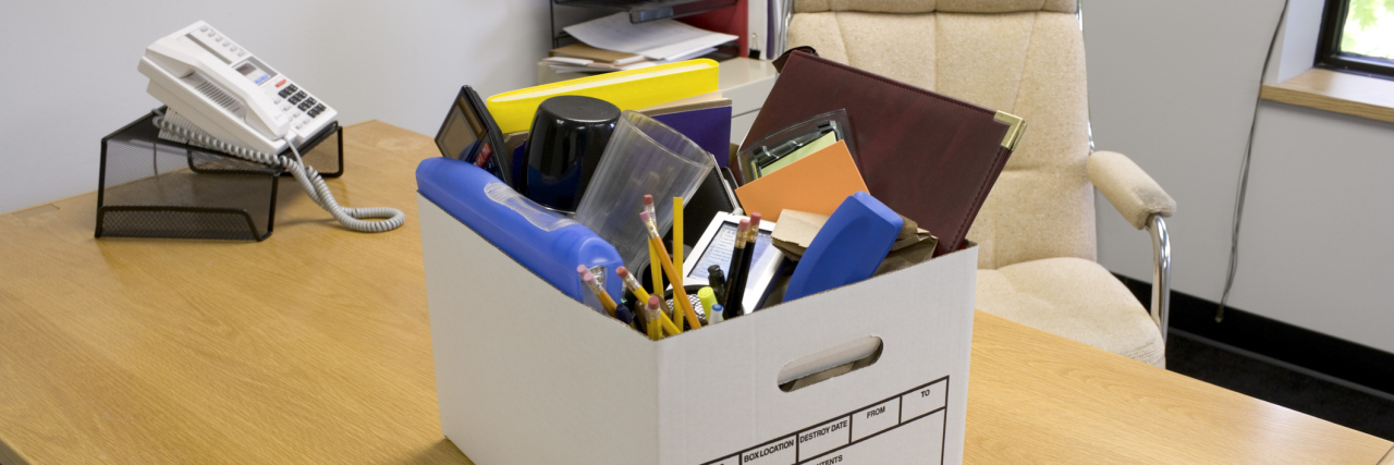 Box of office supplies on desk.