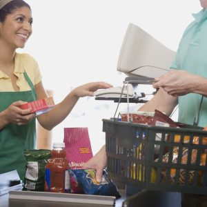 Man at check out counter in grocery store.