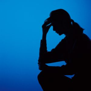 silhouette of a woman holding her head against a blue background