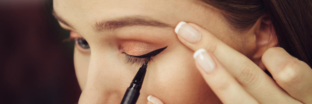 woman putting on eyeliner