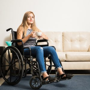 A woman sitting in a wheel chair, drinking a cup of coffee.