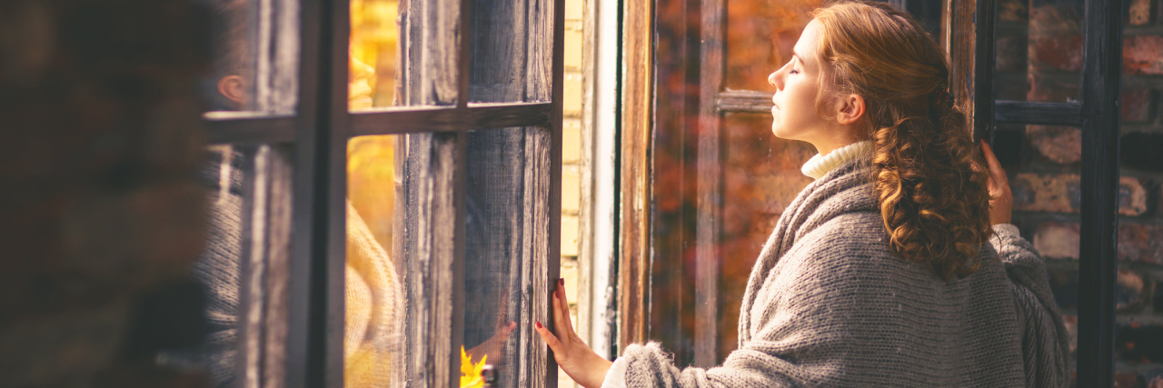 A woman looking outside her window, out into the fall.