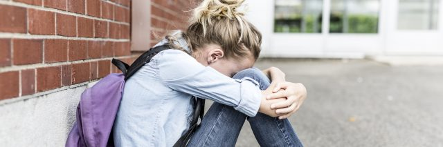 depressed teenage girl at school hugging knees sitting against wall