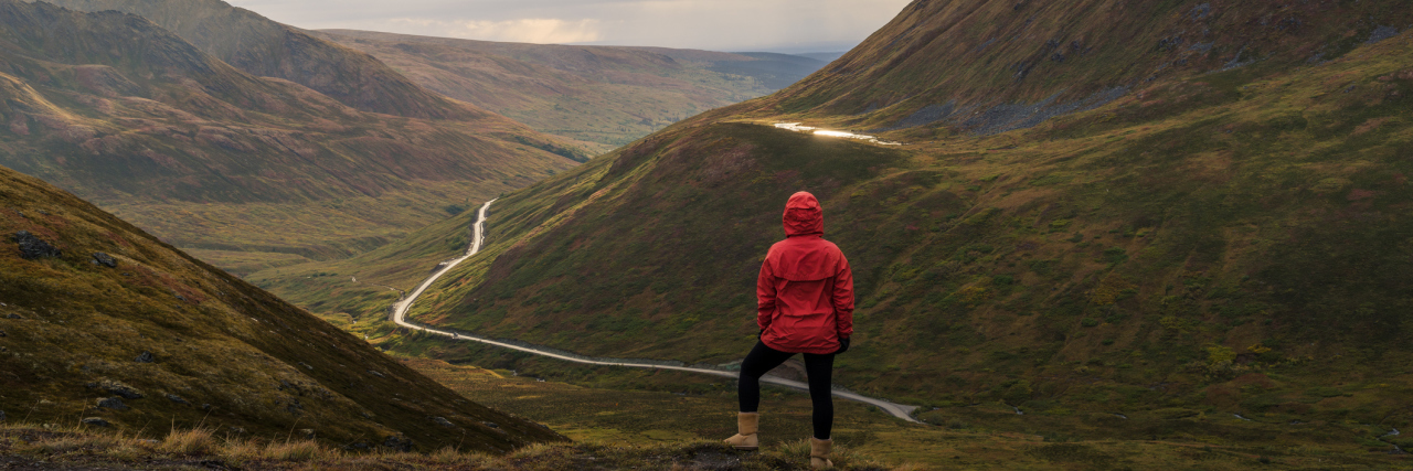 woman in a red jacket standing on top of a mountain looking down at small winding path