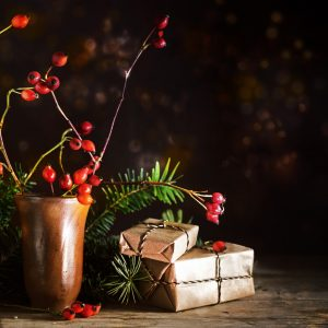 Christmas gift boxes among fir branches and rose hips on a rustic wooden table.