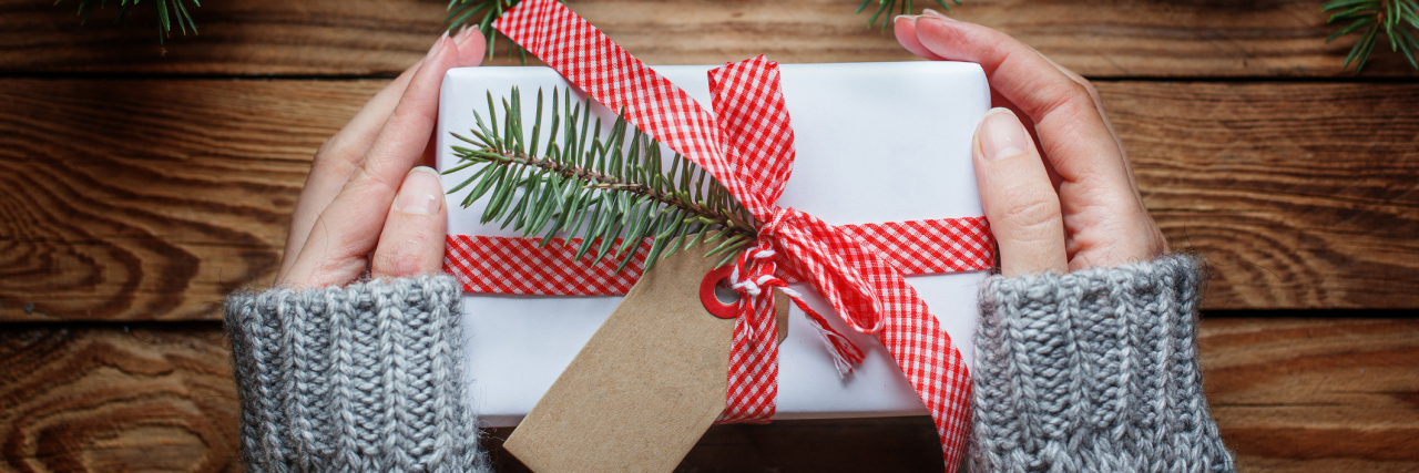 Woman's hands holding christmas present in paper white with red ribbon. Top view.