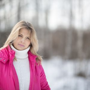 A photo of a woman wearing a jacket out in the snow.
