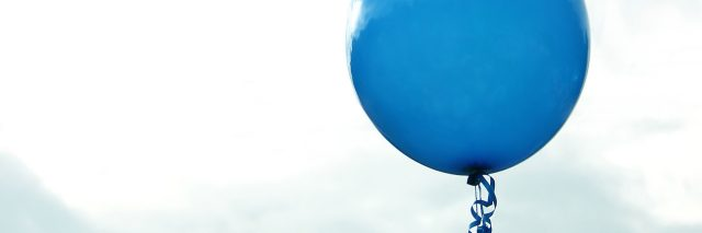 blue birthday balloon against sky with clouds