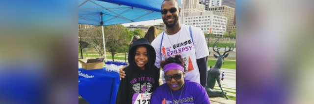 man, woman and a young girl wearing epilepsy awareness shirts