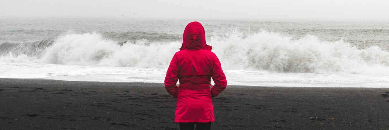 woman stands in front of ocean in a red jacket
