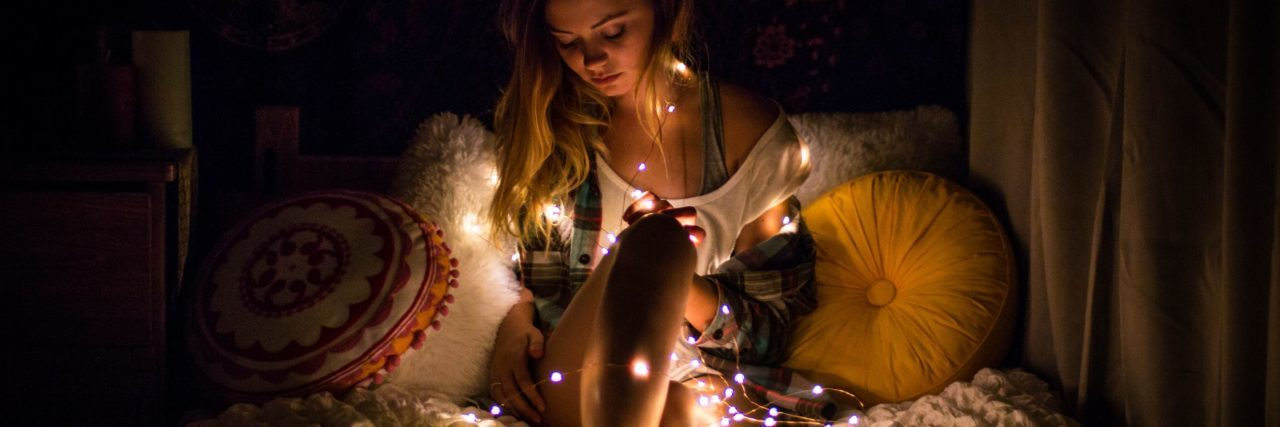young blonde woman sitting on bed surrounded by fairy lights