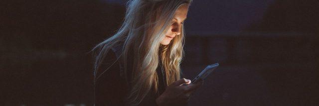 blonde woman at night looking at phone
