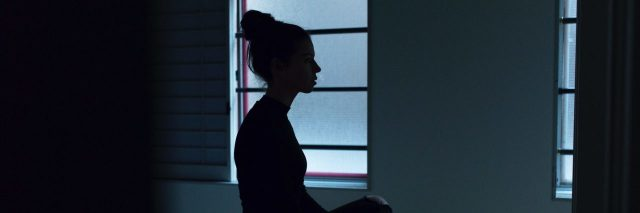 young woman sitting on bed silhouetted against windows