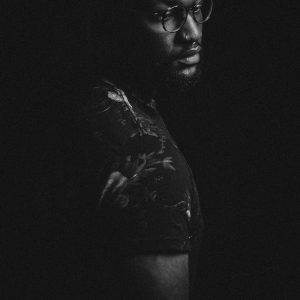 black man wearing glasses standing in darkness