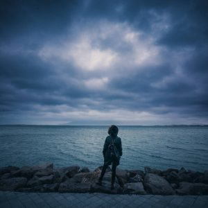 woman in coat standing in front of stormy skies and the ocean
