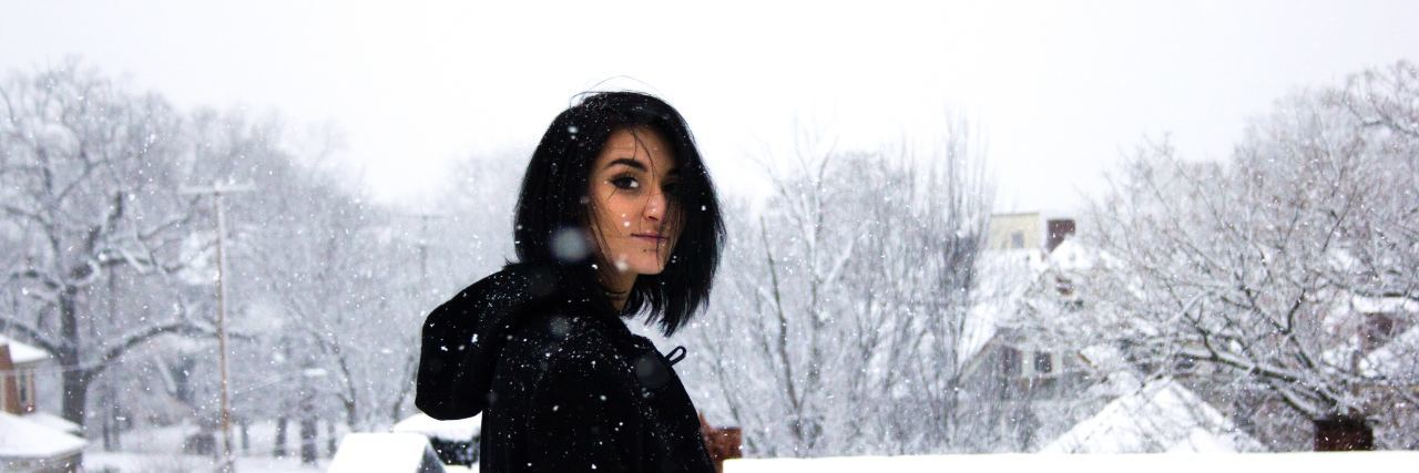 teenager with short black hair stands outside in the snow