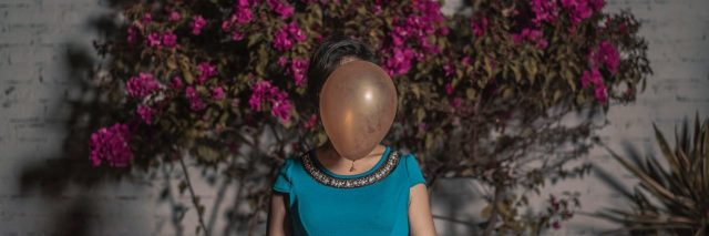 woman in front of pink flowers in blue dress with balloon covering face