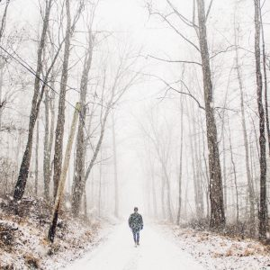 man walking alone in snowy woods