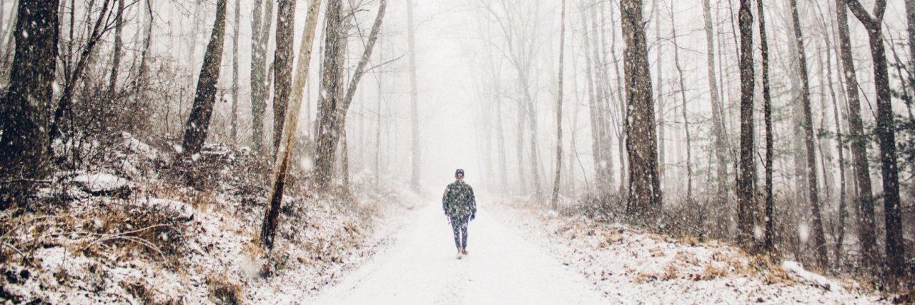 man walking alone in snowy woods