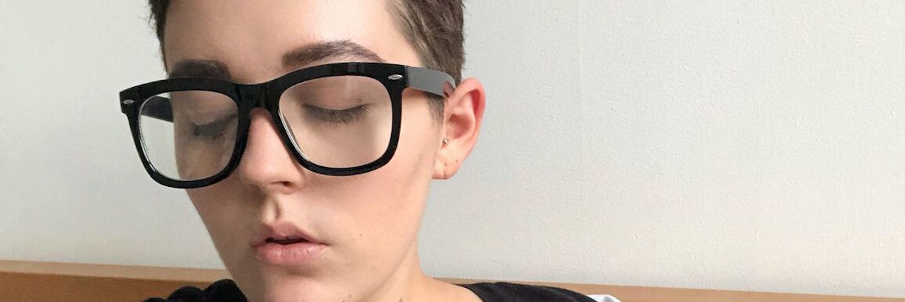 woman with short hair and glasses looks away from the camera