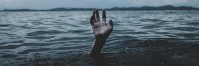 person in stormy ocean with only hand visible drowning