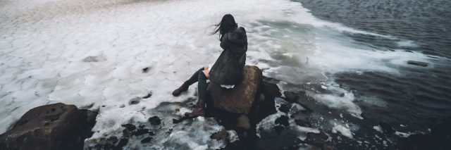 woman sitting in ice and ocean on rock in iceland gray color