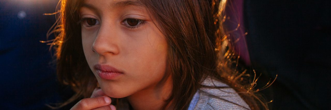 young girl looking upset or pensive with fingers on chin