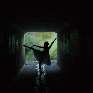 woman dancing silhouetted against light at end of tunnel