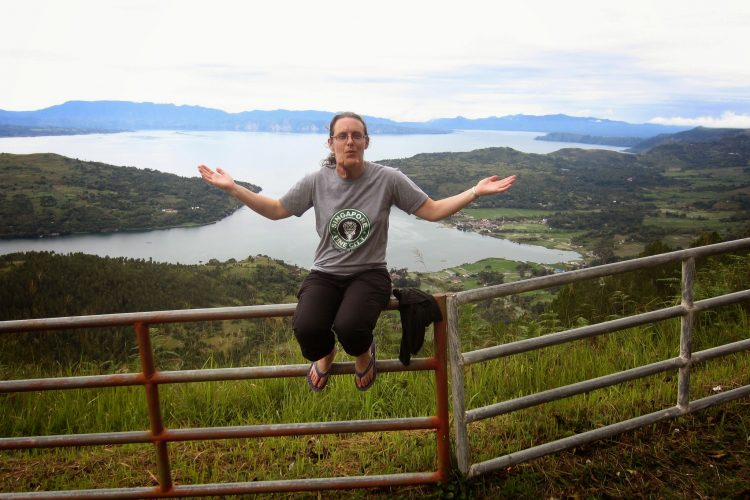 woman sitting on a fence overlooking a lake and mountains in indonesia