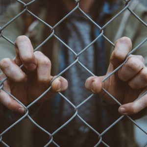 hands holding mesh fence