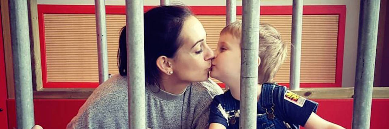 mom kissing her son as the play together