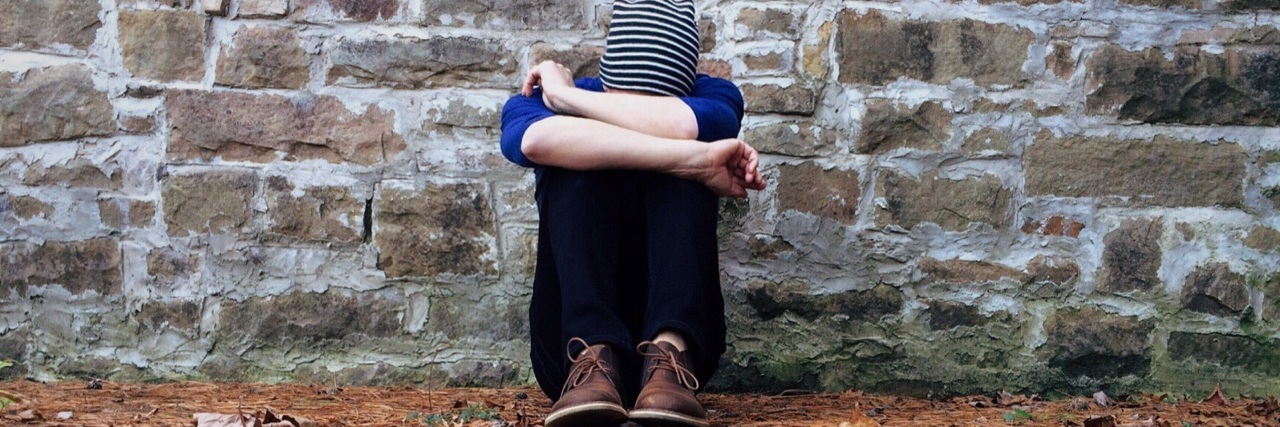 a person sitting outside against a brick wall with their head in their arms