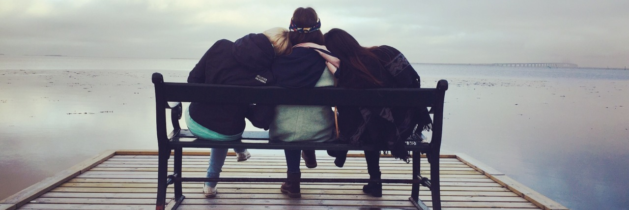 three friends sitting on bench facing end of dock over water