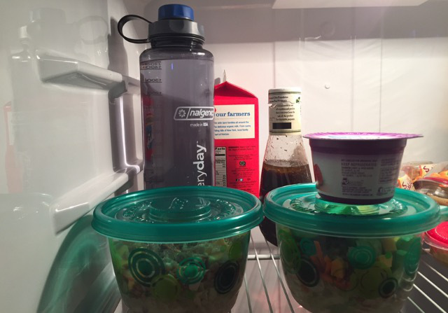 two salads in the fridge with a water bottle