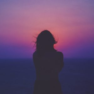 woman alone silhouetted against pink and purple sunset sky