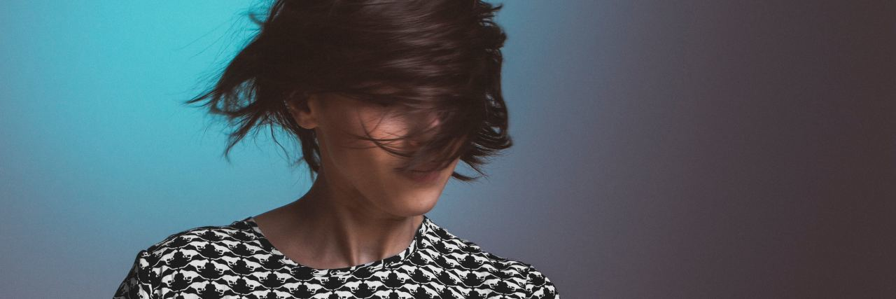 woman with short dark hair swinging her hair in front of her face