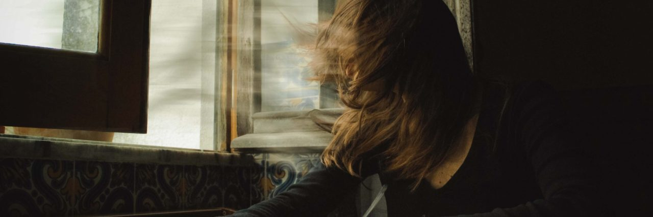 surreal image of girl with windswept hair beside window sat at table
