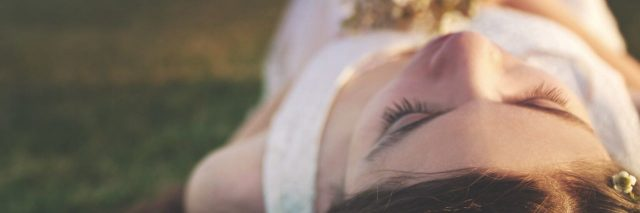 young woman laying on ground with flowers in her hair