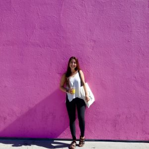 The writer standing in front of a purple wall.